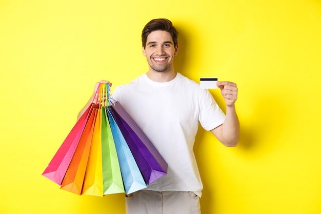 Młody mężczyzna robi zakupy na wakacje, trzymając papierowe torby i polecając bankową kartę kredytową, stojąc na żółtym tle.