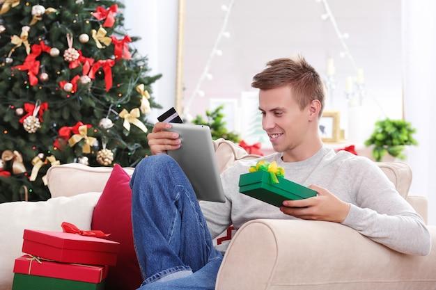 Młody mężczyzna robi zakupy online z kartą kredytową w domu na boże narodzenie