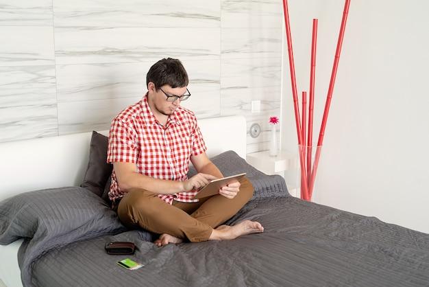 Młody mężczyzna robi zakupy w internecie z tabletem
