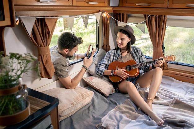 Młody mężczyzna robi zdjęcie swojej dziewczyny z gitarą