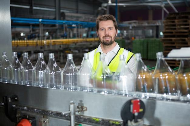 Młody mężczyzna robotnik stojący przy linii produkcyjnej w fabryce soków