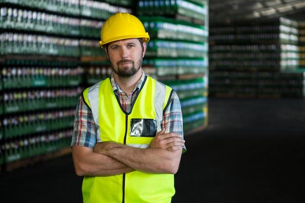 Młody mężczyzna robotnik stojący w magazynie