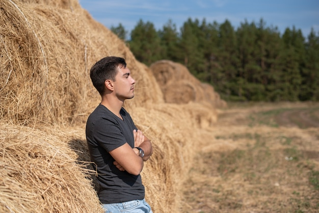 Młody mężczyzna rolnik w szary t-shirt stojący w stogu siana, patrząc z boku