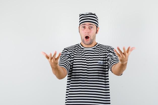 Młody mężczyzna rozciągający ręce w pytającym geście w t-shirt, kapelusz i patrząc zaskoczony. przedni widok.