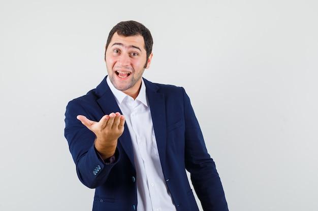 Młody mężczyzna rozciągający rękę w pytającym geście w koszuli, kurtce i patrząc pozytywnie