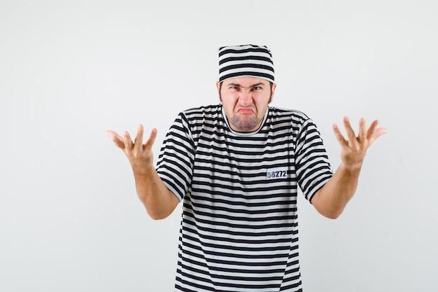 Młody mężczyzna rozciąganie rąk w pytającym geście w t-shirt, kapelusz i patrząc ponury, widok z przodu.