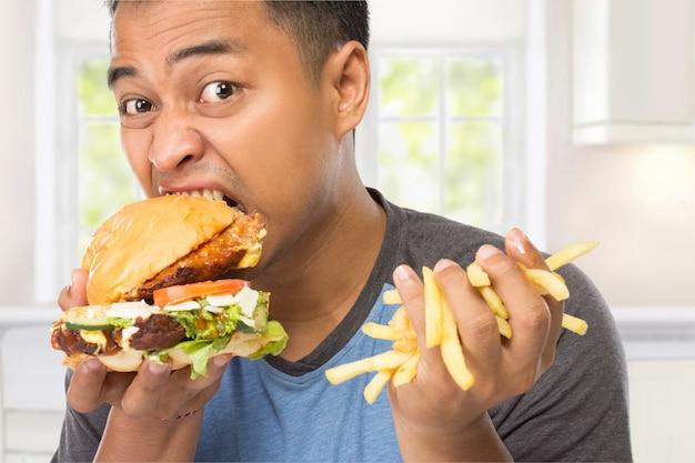 Młody mężczyzna rozgryza przepysznie swojego dużego burgera