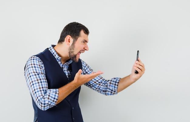 Młody mężczyzna rozmawia na czacie wideo w koszuli, kamizelce i patrząc zły