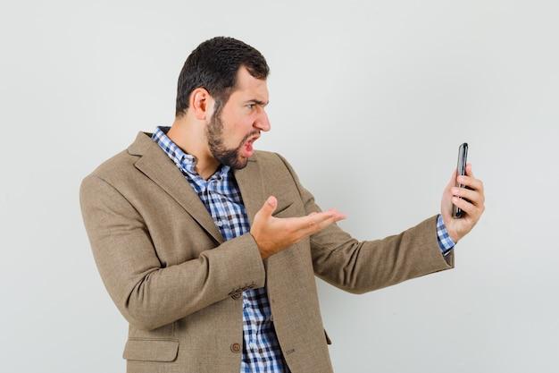 Młody mężczyzna rozmawia na czacie wideo w koszuli, kurtce i patrząc zły