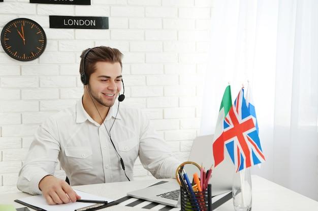 Młody mężczyzna rozmawia na zestaw słuchawkowy w biurze firmy turystycznej