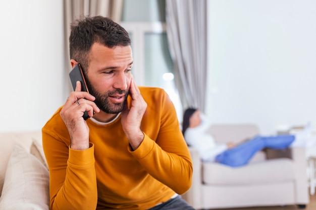 Młody mężczyzna rozmawia prywatnie przez telefon komórkowy, podczas gdy jego żona ogląda telewizję z tyłu.