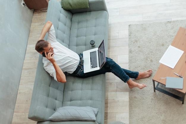 Młody mężczyzna rozmawia przez smartfona siedzącego na kanapie