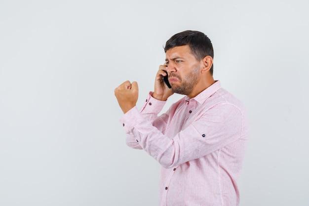 Młody mężczyzna rozmawia przez telefon komórkowy z zaciśniętą pięścią w różowej koszuli i wygląda nerwowo, widok z przodu.