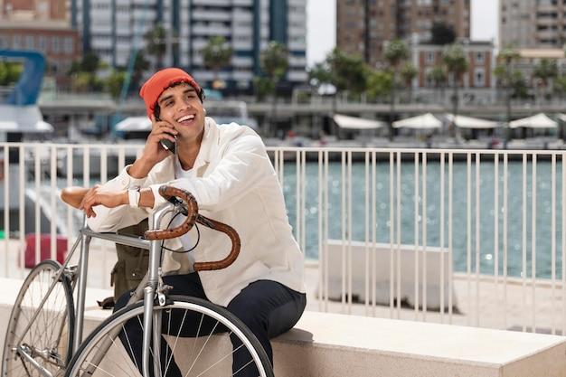 Młody mężczyzna rozmawia przez telefon obok swojego roweru