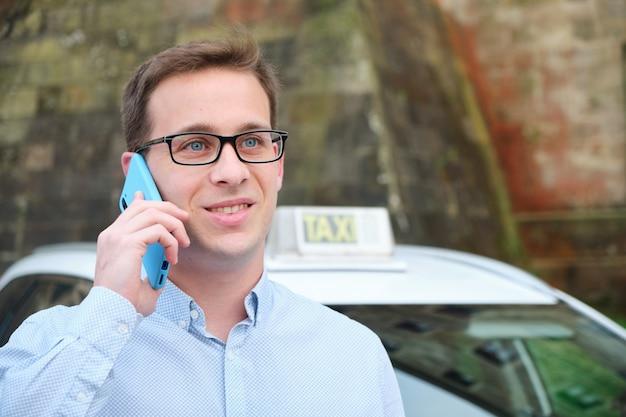 Młody mężczyzna rozmawia przez telefon obok taksówki