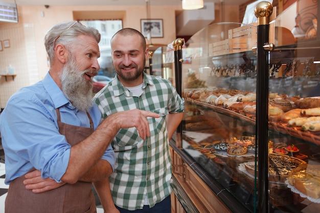 Młody mężczyzna rozmawia ze starszym piekarzem podczas zakupów ciasta w lokalnej piekarni