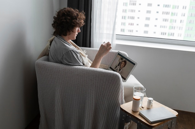 Młody mężczyzna rozmawia ze swoim lekarzem przez wideokonferencję