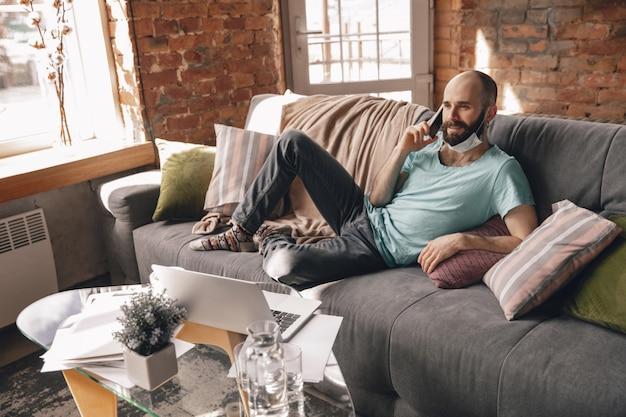 Młody mężczyzna rozmawiający przez telefon w domu podczas kwarantanny i pracy jako freelancer