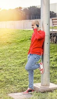 Młody mężczyzna rozmawiający przez telefon w parku, uśmiechnięty