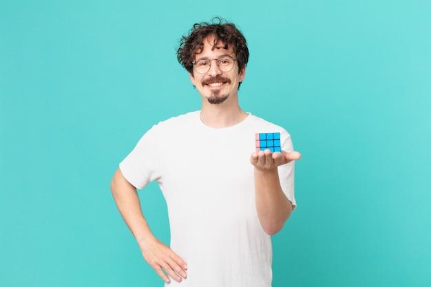 Młody mężczyzna rozwiązujący problem inteligencji, uśmiechający się radośnie z ręką na biodrze i pewny siebie