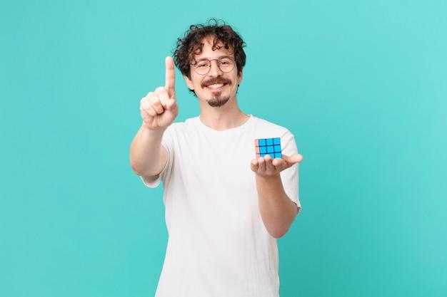 Młody mężczyzna rozwiązujący problem z inteligencją, uśmiechający się dumnie i pewnie robiąc numer jeden