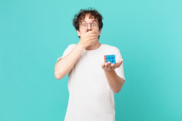 Młody mężczyzna rozwiązujący problem z inteligencją zakrywający usta dłońmi w szoku