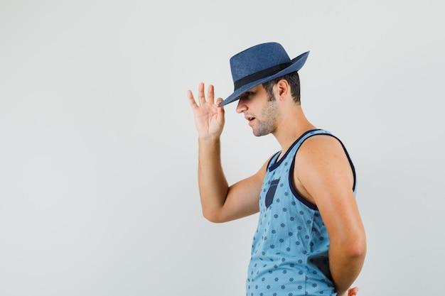 Młody mężczyzna ściąga kapelusz na oczy w niebieskim podkoszulku i wygląda elegancko.