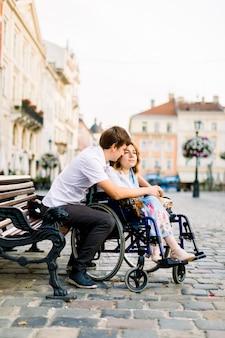 Młody mężczyzna ściska swoją kobietę na wózku inwalidzkim od tyłu, siedząc na ławce na ulicy starego miasta