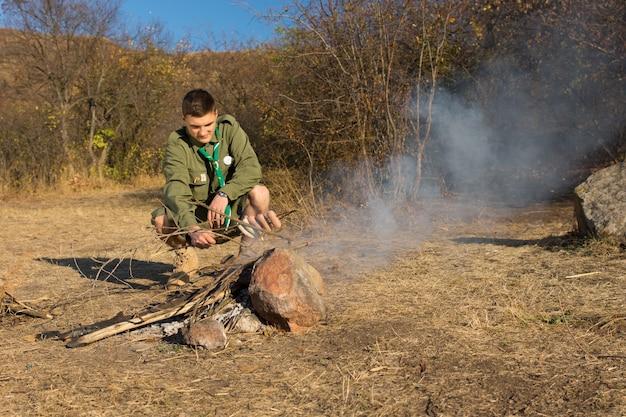Młody mężczyzna scout grillowanie kiełbasek sam w stary sposób na trawiastym campingu.