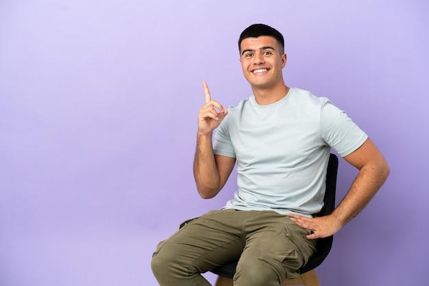 Młody mężczyzna siedzący na krześle na białym tle, wskazując palcem wskazującym, to świetny pomysł