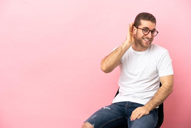 Młody mężczyzna siedzący na krześle na odosobnionym różowym tle, słuchający czegoś, kładąc rękę na uchu