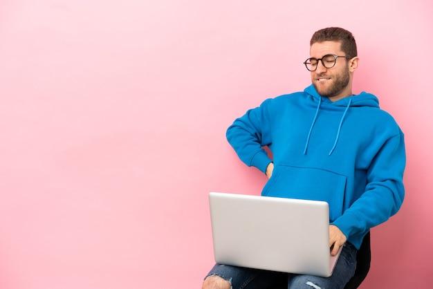 Młody mężczyzna siedzący na krześle z laptopem cierpiący na ból pleców za wysiłek having
