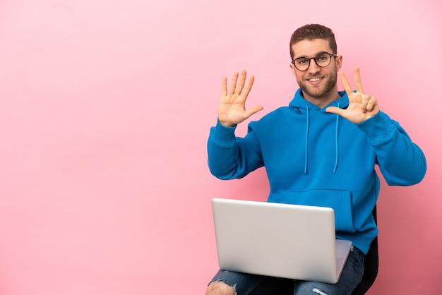 Młody mężczyzna siedzący na krześle z laptopem, liczący osiem palcami