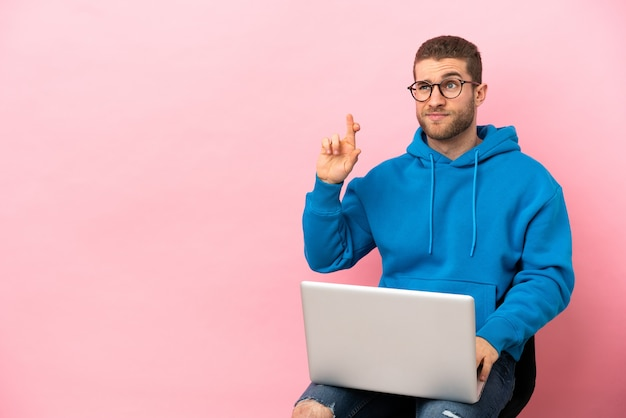 Młody mężczyzna siedzący na krześle z laptopem, skrzyżowanymi palcami i życzącymi wszystkiego najlepszego
