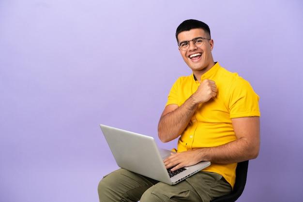 Młody mężczyzna siedzący na krześle z laptopem świętujący zwycięstwo