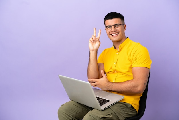 Młody mężczyzna siedzący na krześle z laptopem uśmiechający się i pokazujący znak zwycięstwa