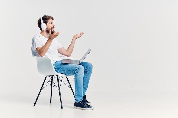 Młody mężczyzna siedzący na krześle z laptopem w technologii słuchawek