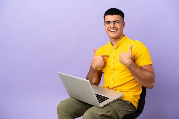 Młody mężczyzna siedzący na krześle z laptopem z niespodzianką wyrazem twarzy