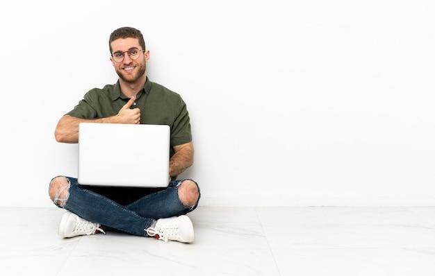 Młody mężczyzna siedzący na podłodze, dający kciuk w górę gestu
