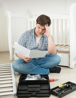 Młody mężczyzna siedzący na podłodze i czytający skomplikowaną instrukcję montażu łóżeczka dla dziecka