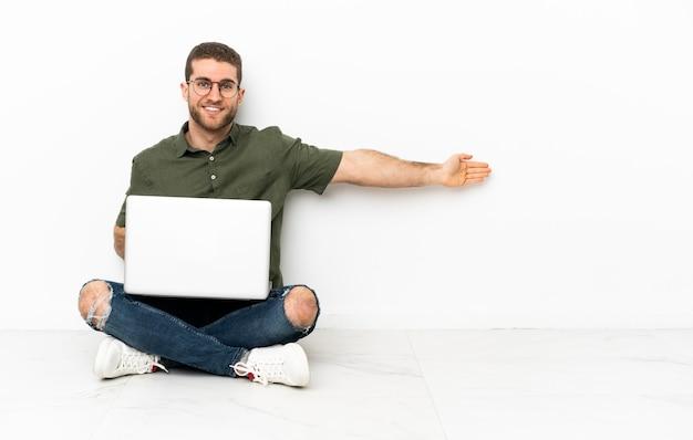 Młody mężczyzna siedzący na podłodze, wyciągając ręce do boku, zapraszając do przyjścia