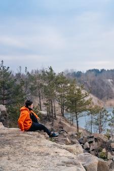 Młody mężczyzna siedzący na skraju urwiska