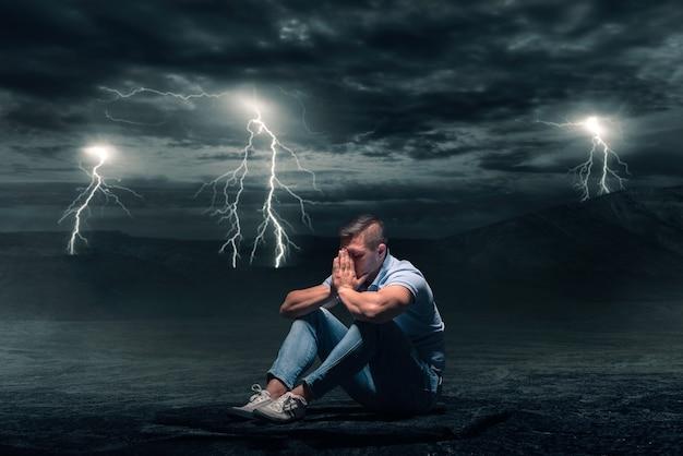 Młody mężczyzna siedzący na ziemi na pustyni, burza z błyskiem pioruna