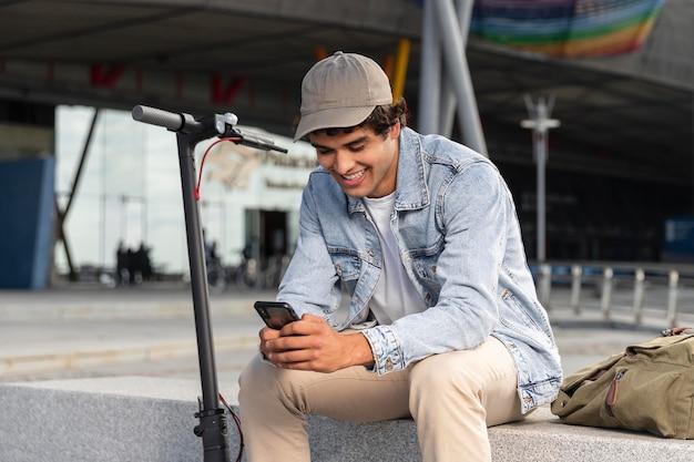Młody mężczyzna siedzący obok skutera