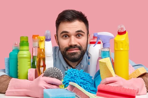 Młody mężczyzna siedzący obok środków czyszczących