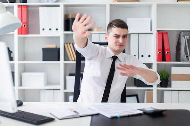 Młody mężczyzna siedzący przy biurku komputerowym w biurze i rozkładający ręce na bok.