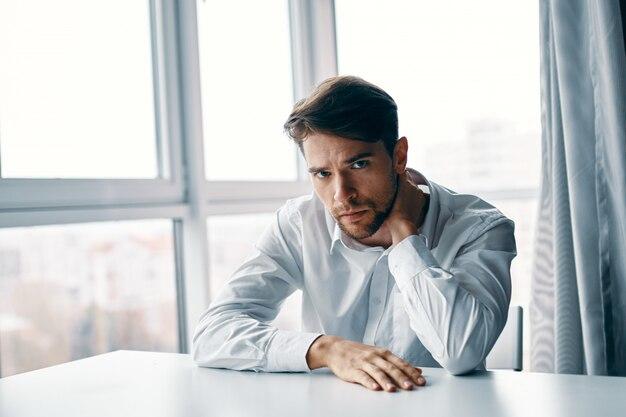 Młody mężczyzna siedzący przy stole przygnębiony w stosunku do okna