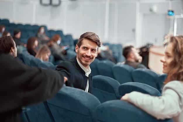 Młody mężczyzna siedzący w sali wykładowej centrum biznesowego