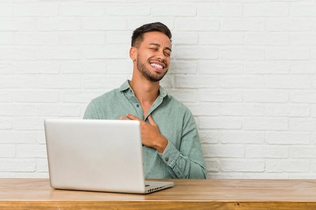 Młody mężczyzna siedzący z laptopem śmieje się głośno, trzymając rękę na piersi