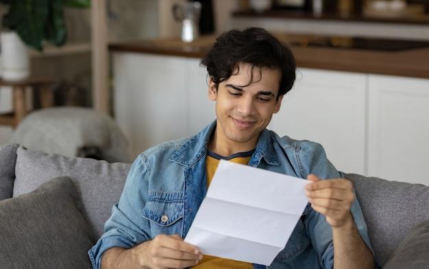 Młody mężczyzna siedzi i czyta dobre wieści w papierowym powiadomieniu o liście rekrutacyjnym do nowej pracy lub świetnym wyniku egzaminu na kanapie w domu